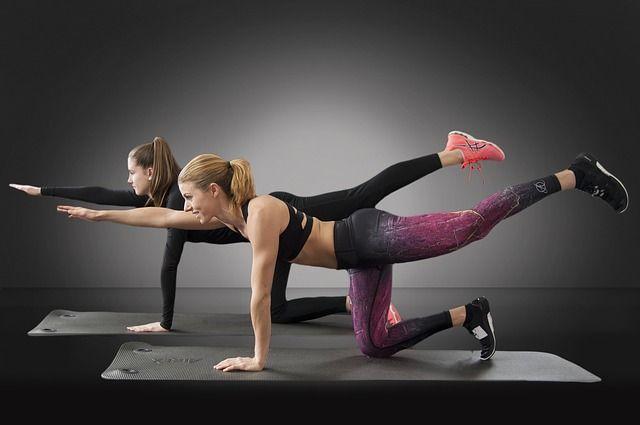 マットの上でインナーマッスルを鍛える二人の女性